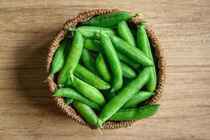 a colheita de ervilhas encontra-se em uma cesta de vime redonda sobre um fundo de madeira foto