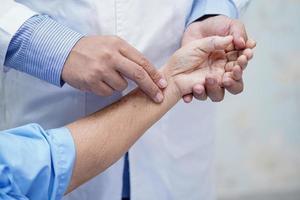 médico segurando mãos comoventes paciente asiática sênior com amor foto