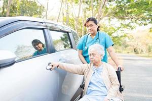 médico ajuda paciente idosa asiática sentada na cadeira de rodas para o carro foto