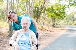 ajuda e cuidado mulher asiática sênior usar walker no parque. foto