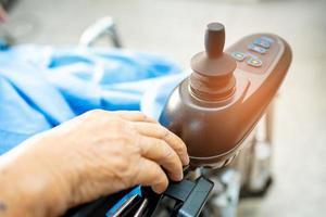 paciente idosa asiática em cadeira de rodas elétrica no hospital foto