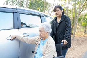 ajudar paciente idosa asiática sentada na cadeira de rodas para o carro foto