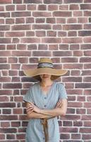 retrato de uma bela jovem em um fundo de tijolos vermelhos foto
