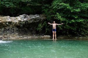 homem nadando no rio da montanha com uma cachoeira foto