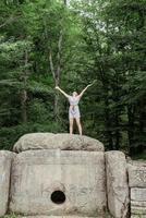 jovem de pé em uma grande pedra na floresta, olhando para longe foto