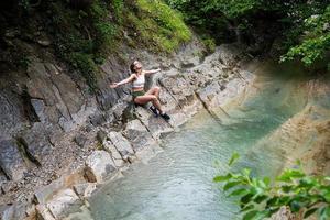 jovem mulher feliz curtindo a natureza, sentada à beira do rio da montanha. foto
