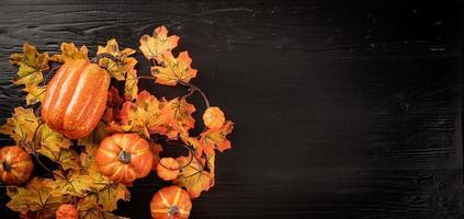 decorações de outono com abóboras e folhas, vista superior em preto foto