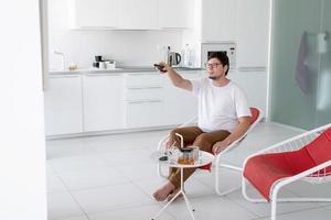 homem sentado em uma cadeira assistindo TV segurando o controle remoto foto