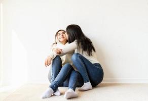 duas melhores amigas sentadas juntas em casa se beijando foto