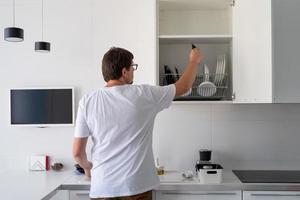homem de camiseta branca lavando pratos na cozinha foto