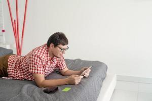 jovem comprando na internet com o tablet foto