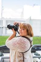 retrato de mulher obesa tirando fotos com uma câmera ao ar livre