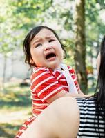 menina asiática chorando nas mãos da mãe foto