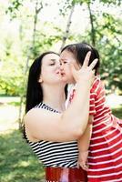 mãe beijando e acalmando sua filha bebê foto