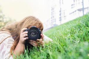 retrato de mulher obesa tirando fotos com uma câmera no parque