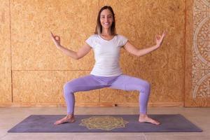 mulher fazendo pose de deusa em ioga foto