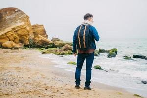 homem com uma mochila em pé sobre uma rocha contra um lindo mar foto