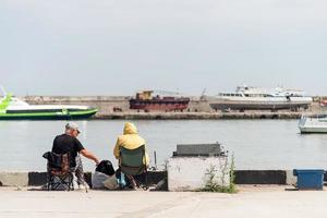 pessoas pescando no aterro, barcos e iates ao fundo foto