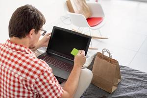 vista traseira de homem comprando na internet com laptop olhando foto