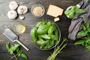 preparando molho pesto italiano, manjericão e ingredientes na mesa preta foto