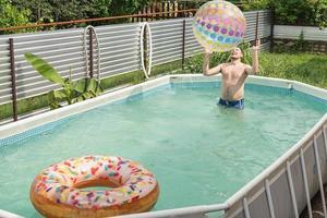 homem se divertindo na piscina, brincando com bola inflável foto