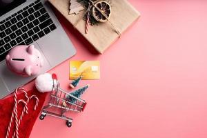 decorações de natal e cofrinho em fundo rosa foto
