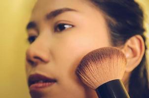 rosto de beleza de mulher asiática, aplicando pincéis na pele por cosméticos. foto