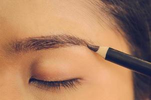 rosto de beleza de mulher asiática, aplicando o lápis de sobrancelha na pele. foto