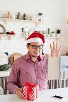 homem com chapéu de Papai Noel cumprimentando seus amigos em um bate-papo por vídeo ou uma ligação no tablet foto
