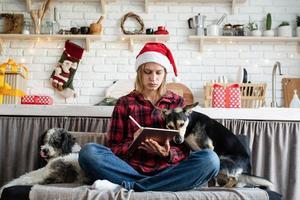 jovem loira com chapéu de Papai Noel trabalhando em um tablet sentada no sofá foto