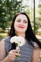 morena adulta de meia-idade em pé ao ar livre sentindo o cheiro de flores frescas foto