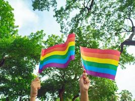 duas mãos seguram pequenas bandeiras do arco-íris do movimento lgbtq foto