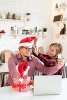 casal com chapéu de Papai Noel cumprimentando seus amigos em uma videochamada no tablet foto
