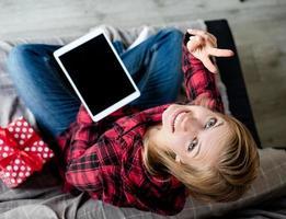 jovem loira trabalhando em um tablet, sentada no sofá, vista de cima foto