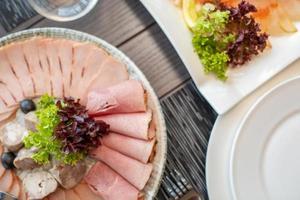 corte de salsicha e carne curada em uma mesa comemorativa. foto