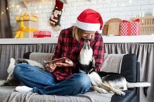 mulher com chapéu de Papai Noel trabalhando em um tablet sentada no sofá com o cachorro foto