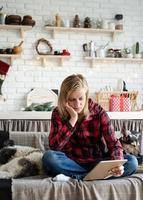 jovem mulher triste trabalhando em um tablet, sentada no sofá foto