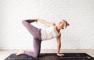 mulher loira praticando ioga em casa foto