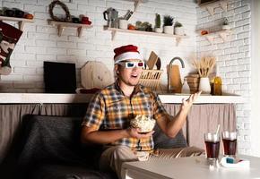 jovem com óculos 3D assistindo filmes em casa à noite no natal foto
