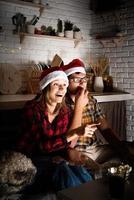casal assistindo filmes em casa no natal apontando para a tela foto