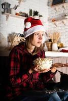 mulher com chapéu de Papai Noel assistindo filmes em casa na noite de natal foto