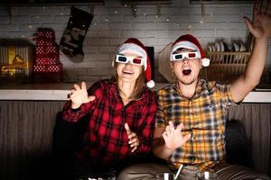 jovem casal em óculos 3D assistindo filmes em casa no natal foto