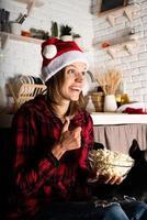 mulher assistindo filmes em casa na noite de natal comendo pipoca foto