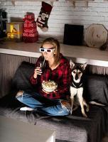 mulher com óculos 3D assistindo filmes em casa à noite no natal foto