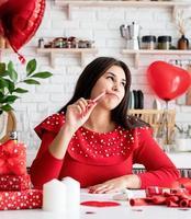 mulher escrevendo carta de amor sentada na cozinha decorada foto