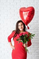 mulher segurando flores e um balão de coração vermelho foto