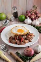 arroz frito de manjericão sagrado com coração de galinha e ovo frito foto