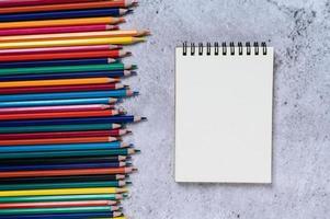um livro e vista de cima de lápis de cor com bloco de notas transparente foto