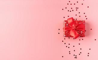 caixa de presente vermelha com laço de corda em fundo rosa foto