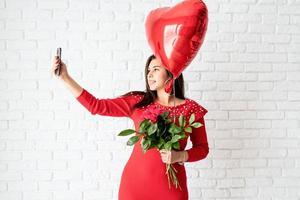 jovem de vestido vermelho segurando flores e um balão de coração vermelho foto